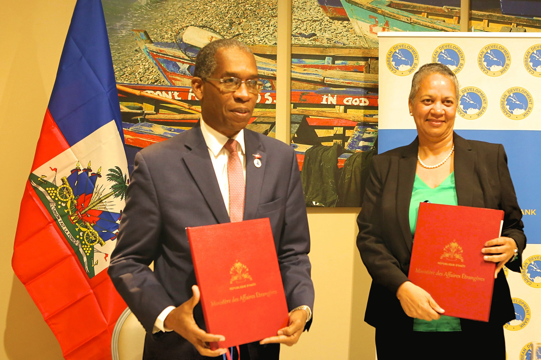 Haiti's Minister of Foreign Affairs, His Excellency Antonio Rodrigue (left) and Vice-President (Operations), Caribbean Development Bank (CDB), Monica La Bennett (right), hold the signed country agreements after signing them on February 27, 2018. CDB will establish its first country office in the Republic of Haiti this year.