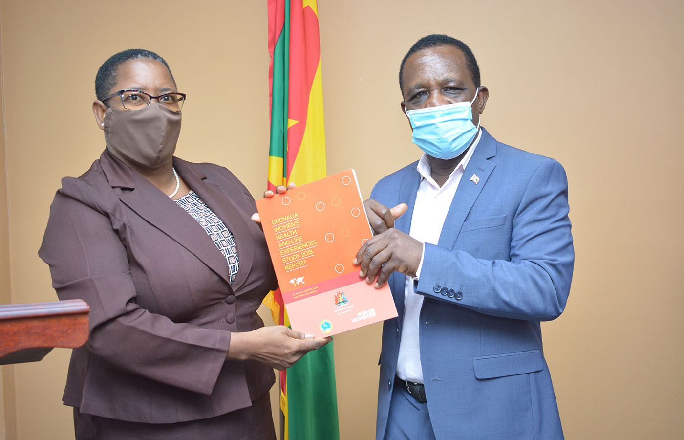 Elaine McQueen in brown suit presents publication to Prime Minister, Dr. Keith Mitchell who is wearing a blue suite. Grenada's flag is int he background