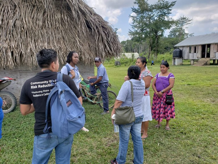 group of persons outside a village in Belize