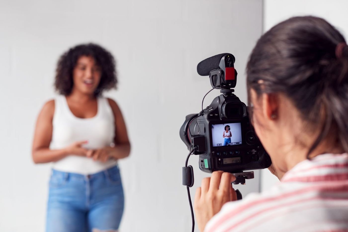 Female videographer recording young woman in white top and jeans.