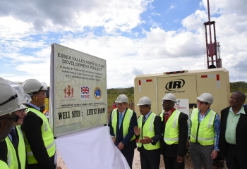 Government officials and stakeholders wear protective gear on a drill site for a project in Jamaica