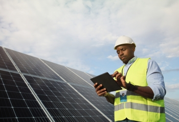 Technician in yellow jacket standing next to solar panels
