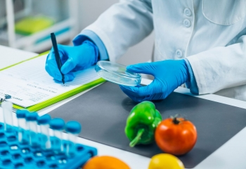 lab tech in white jacket and blue gloves with vegetables and vials on desk