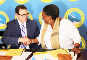 CDB President Smith (l.) and Prime Minister of Barbados Mottley shaking hands after signing the loan