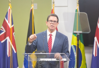 CDB President Dr Wm Warren Smith wearing blue suit and red tie, standing at a transparent lectern