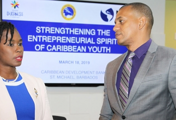 CDB Director of Project Daniel Best (at right in grey suit), in conversation with Executive Director of the Barbados Youth Business Trust Cardell Fergusson (in blue dress with of white jacket)