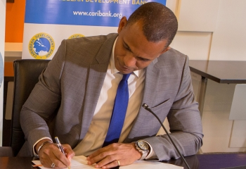 Daniel Best wearing grey suit with blue tie signing document.