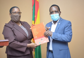 Elaine McQueen in brown suit and mask presents report to Prime Minister, Dr. Keith Mitchell who is wearing a blue suit and mask. The Grenada flag is in the background.