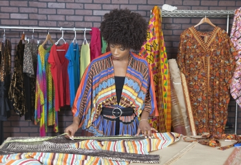 Female fashion designer measuring fabric surrounded by colourful outfits