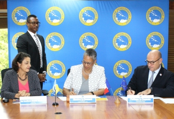Vice-President (Operations) of the Caribbean Development Bank, Monica La Bennett (center) and Philippe La Cognata, Atlantic Regional Director, Agence Française De Développement (right) sign the finance agreement. At left, Ambassador Daniela Tramacere, Head of the European Union Delegation to Barbados, the Eastern Caribbean, OECS and CARICOM/CARIFORUM and CDB Senior Legal Counsel Dave Waithe (second from left) look on.