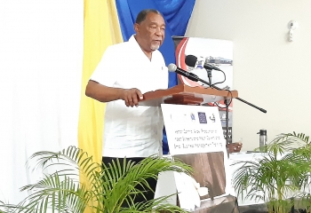 older gentleman in white shirt and black slacks standing at a wooden lectern