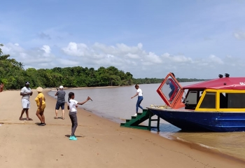 People disembarking onto a beach from a boat tour