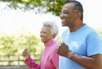 Smiling older couple jogging