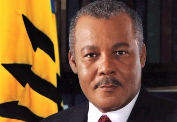 Photo of Prime Minister Owen Arthur with Barbados flag in background to left.