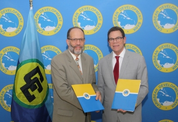 CARICOM SEcretary General Irwin LaRocque and CDB President Dr Warren Smith shaking hands.