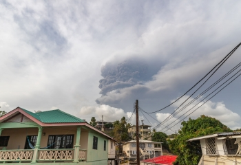 clouds of ash rise above homes in St. Vincent after volcano eruption