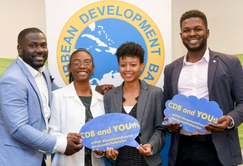Four smiling young people holding youth-focused social media props