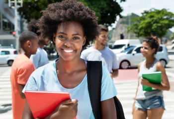 Smiling young woman with Afro hairstyle holding notebook.