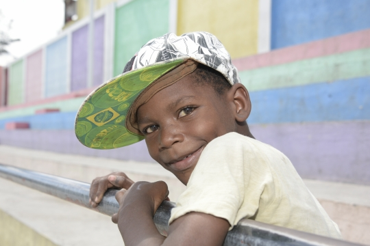 young boy with cap on looking into the camera